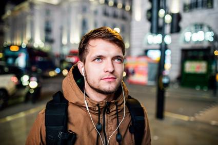 夜に通りを歩いている男性