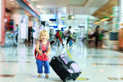 空港でスーツケースを持つ小さな女の子