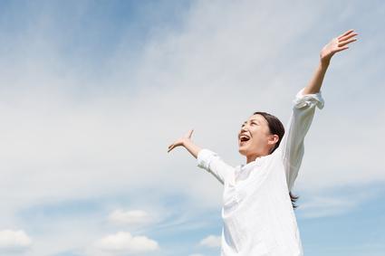 青空に向かって手を広げている女性