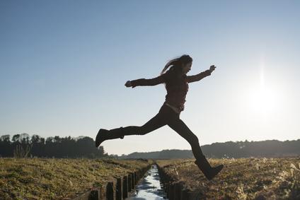 小川を飛び越える女性
