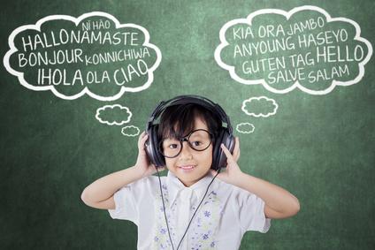 ヘッドフォンで外国語を聞く女の子
