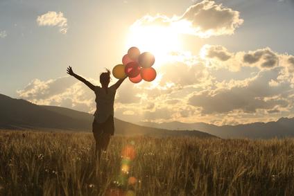 風船で日暮れ草原の上を走る女性
