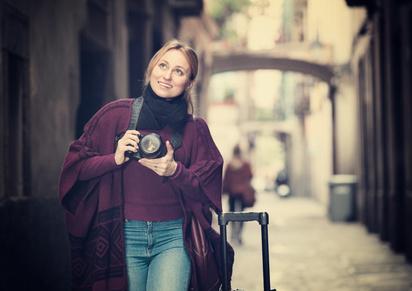 写真を屋外で撮っている若い女性