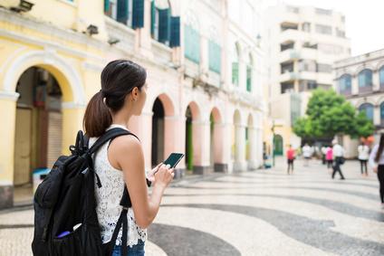携帯電話を使うバックパッカーの女性